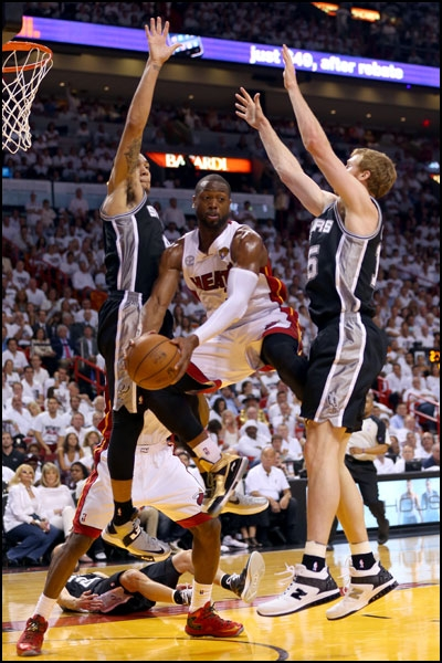 Dwyane Wade of the Miami Heat drives against the San Antonio Spurs' bigs.