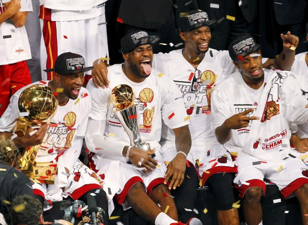 Heat's James holds the Bill Russell MVP Trophy as Wade (L) holds the Larry O'Brien Trophy while Bosh celebrates after their team defeated the Spurs in Game 7 to win their NBA Finals basketball playoff in Miami